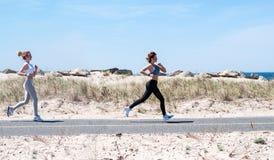 Fitness girls running on beach. Fitness women running on beach. Happy girls women jogging outdoors Royalty Free Stock Images