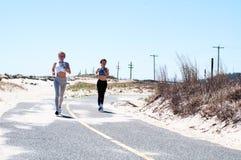 Fitness girls running on beach. Fitness women running on beach. Happy girls women jogging outdoors Royalty Free Stock Photography