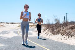 Fitness girls running on beach. Fitness women running on beach. Happy girls women jogging outdoors Stock Images