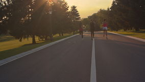 Fitness women running on park road. Women group running outdoors at sunset stock footage