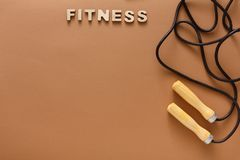Fitness, jumping rope on black background. Fitness word and jumping rope on brown background. Skipping rope, sport supply, weightloss, slimming concept, top view Royalty Free Stock Photography