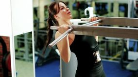 Fitness workout, brunette woman at gym, girl performs a pulling up exercise, exercises on the horizontal bar, healthy stock footage
