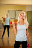 Fitness workout - fit woman training with dumbellc in gym Stock Images