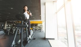 Fitness workout. Girl exercising on elliptical trainer in gym royalty free stock images