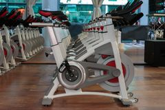 Fitness Workout in Gym: Group of Modern Spinning Bikes in Line.  Stock Images