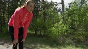 Fitness workout outdoors. Sport woman running through the woods. She`s in a good mood and a great figure. Deciduous