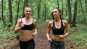 Fitness workout outdoors. Two slender brunette with long hair running through the woods and communicate. They are smiling. Video shot on the Sony camera, slow stock video