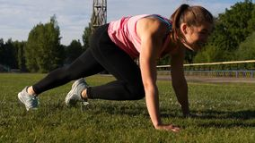 Young Fit Woman Exercising on Green Grass in Park