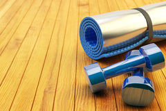 Fitness workout and slimming exercises concept. Weight loss gym equipment: blue yoga mat and dumbbells on wooden floor of training class Royalty Free Stock Images