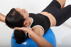 Fitness workout by young woman using exercise ball Royalty Free Stock Photos