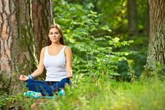 Fitness yoga exercise in wood. Young woman healthy lifestyle portrait. In nature royalty free stock photography