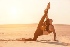 Fitness yoga woman stretching on sand. Fit female athlete doing yoga pose. royalty free stock photography