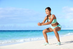 Fitness young Asian woman training legs with squat exercise on beach. Fitness young woman working out core and glutes with bodyweight workout doing squat Stock Images
