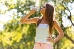 Fitness beautiful woman drinking water after exercising at the park stock photography