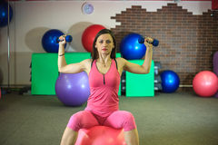 Fitness. Young beautiful white girl in pink sports suit does physical exercises with dumbells and fit ball at the fitness center. Stock Photos