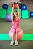 Fitness. Young beautiful white girl in pink sports suit does physical exercises with dumbells and fit ball at the fitness center. Royalty Free Stock Photos