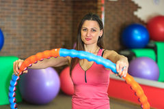 Fitness. Young beautiful white girl in a pink sports suit does physical exercises with a hoop at the fitness center. Royalty Free Stock Photography