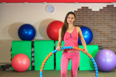 Fitness. Young beautiful white girl in a pink sports suit does physical exercises with a hoop at the fitness center. Royalty Free Stock Images