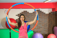 Fitness. Young beautiful white girl in a pink sports suit does physical exercises with a hoop at the fitness center. Stock Images