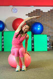 Fitness. Young beautiful white girl in a pink sports suit does physical exercises with a pink fit ball at the fitness center. Stock Photo