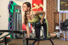 Fitness. Young beautiful white girl in a yellow and gray sports suit is doing exercises with a dumbbell on training apparatus. Royalty Free Stock Photography