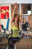 Fitness. Young beautiful white girl in a yellow and gray sports suit is doing exercises on training apparatus in the fitness club. Stock Photos