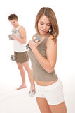 Fitness - Young couple training lifting weights Stock Photo
