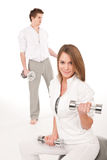 Fitness - Young couple training with weights Stock Photography