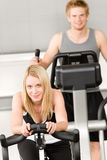 Fitness young girl on gym bike. Crosstrainer in background stock photos
