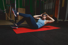 Fitness young girl in the gym doing exercises with abdominals. Crossfit.  Stock Photography