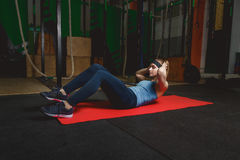 Fitness young girl in the gym doing exercises with abdominals. Crossfit.  Royalty Free Stock Images