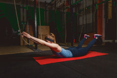 Fitness young girl in the gym doing exercises with abdominals. Crossfit.  Stock Photos