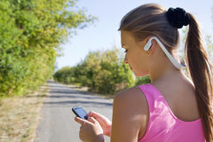 Fitness young girl with phone and headphones. Before jogging Stock Photo