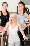 Fitness young girls at gym posing. Fitness young girls on gym bike indoor cardio exercise posing royalty free stock images
