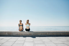 Fitness young girls relaxing after running in city. Happy sporty fit young interracial friends enjoying view of sea after jogging training outside Stock Photography