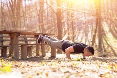 Fitness young man doing push ups or plank. In nature stock photography