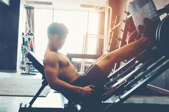 Fitness young man exercising using rowing machine in the gym royalty free stock photography
