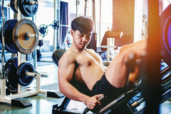 Fitness young man exercising using rowing machine in the gym Stock Photography