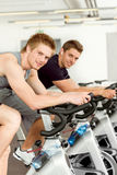 Fitness young man on gym bike spinning. Indoor cardio exercise Stock Photo