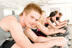 Fitness young man on gym bike spinning royalty free stock photos