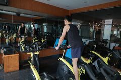 Asian chinese Fitness young man on gym bike spinning. Fitness young man on gym bike spinning indoor cardio exercise Stock Photography