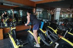 Asian chinese Fitness young man on gym bike spinning. Fitness young man on gym bike spinning indoor cardio exercise Royalty Free Stock Image