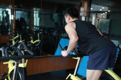 Asian chinese Fitness young man on gym bike spinning. Fitness young man on gym bike spinning indoor cardio exercise Royalty Free Stock Photos