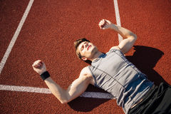 Fitness young man laying on running track after hard workout. At the stadium stock photo