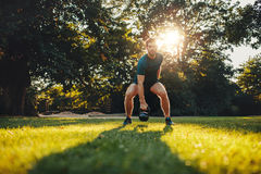 Fitness young man training with kettlebell in the park Stock Photography