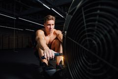 Fitness young man using rowing machine in the gym. Rower bodybuilder trains in the loft space. Torso in shorts. Concentrated motivation stock photos