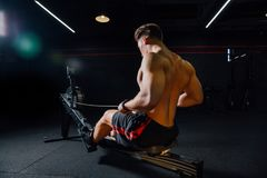 Fitness young man using rowing machine in the gym stock photography