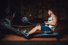 Fitness young man using rowing machine in the gym and screaming royalty free stock photography