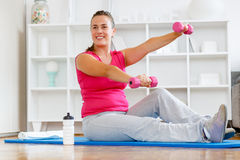 Fitness. Young mother working out with weights after child birth. Getting back into shape Royalty Free Stock Images