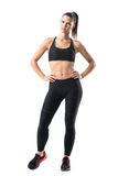 Fitness young pretty woman in black leggings and tank top posing with hands on hips Royalty Free Stock Images